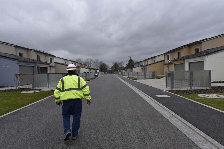 U.S. Army Corps of Engineers, Europe District Project Engineer John Taylor walks down a new street past several recently completed and nearly completed homes May 6, 2021 in the Kittenberg Housing Area on Rose Barracks in Vilseck, Germany, which is part of U.S. Army Garrison Bavaria. The U.S. Army Corps of Engineers is delivering 29 family homes, including associated infrastructure like drainage, utilities and roads in a newly built neighborhood for Soldiers and their families. The homes are part of a larger, long-term collaboration between the U.S. Army Corps of Engineers and the garrison to provide new and renovated family housing and other quality of life projects for Soldiers and their families at Rose Barracks.