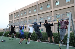 Maj. Anthony Sims-Hall, 1st Theater Sustainment Command, theater mortuary affairs officer, leads a functional fitness workout for Soldiers at Camp Arifjan, Kuwait. Maj. Sims-Hall takes personal passion and hobbies and turns them into resiliency opportunities for Soldiers while deployed.