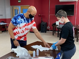 Maj. Anthony Sims-Hall, 1st Theater Sustainment Command, theater mortuary affairs officer, instructs a Soldier on tie-dying techniques at an event held at the MWR building on Camp Arifjan, Kuwait.  Maj. Sims-Hall takes personal passion and hobbies and turns them into resiliency opportunities for Soldiers while deployed.