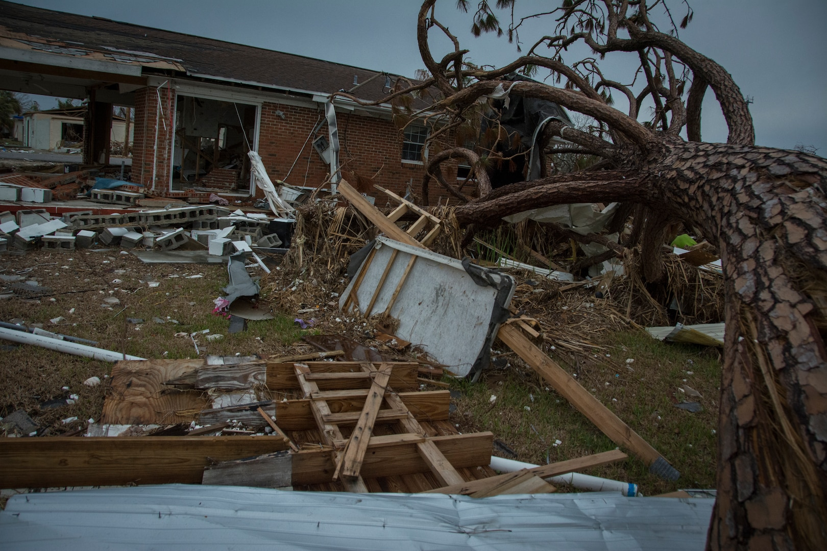 Debris fills a yard in front of a house.