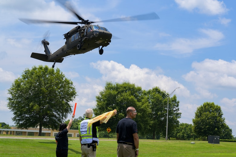 Members of the helicopter landing crew guide in a UH-60 Black Hawk helicopter to a landing zone at Central Georgia Technical College, Warner Robins, Georgia, June 12, 2021.