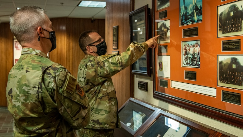 Two Airmen in uniform point at a photo on a wall.