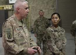 The Commanding General of the 1st Theater Sustainment Command, Maj. Gen. John P. Sullivan, stands with Sgt. 1st Class Michelle Metzger, the senior enlisted advisor for the Fort Bragg, N.C., based 151th Quartermaster Detachment, moments before the general presented his command coin to riggers, Spc. Paulo Paulo and Sgt. Joshua Parkinson, during his June 10, 2021 visit. Metzger recommended the riggers for their hard work and dedication during the deployment.
