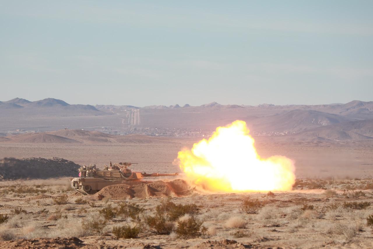 A ball of fire erupts from a tank as it fires on a desert landscape.