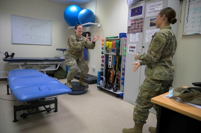 U.S. Air Force Master Sgt. Jessica Brock, physical therapy technician, and Capt. Rebecca Wilder, physical therapist, 380th Expeditionary Medical Group, demonstrate common exercises used during physical therapy sessions, Al Dhafra Air Base, United Arab Emirates, May 26, 2021. Physical therapy services are available at ADAB and include but are not limited to, therapeutic exercise, manual manipulation, and dry needling. (U.S. Air Force photo by Tech. Sgt. Michelle Y. Alvarez)