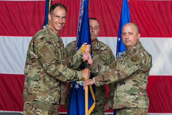 Col. Matt Husemann, left, 436th Airlift Wing commander, passes the 436th Maintenance Group guidon to Col. Bary Flack, new 436th MXG commander, during the 436th MXG Change of Command ceremony on Dover Air Force Base, Delaware, June 11, 2021. Flack took command from Col. Christopher May. The 436th MXG supports the worldwide global mobility mission by providing trained maintenance specialists for two of the Air Force's cargo transport aircraft, the C-5M Super Galaxy and the C-17A Globemaster III. (U.S. Air Force photo by Roland Balik)