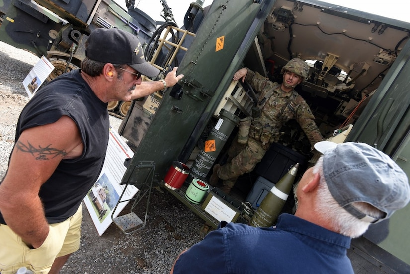 A Soldier with 2nd Battalion, 138th Field Artillery (Paladin), talks shop with former members of the unit about the Paladin's capabilities. (Eric Pilgrim, Fort Knox News)