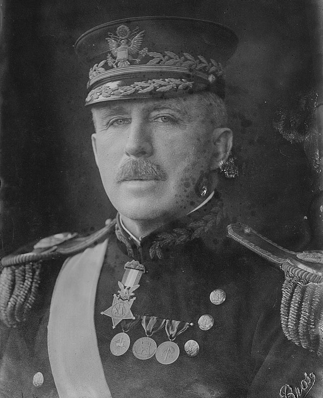 A man in military dress with many decorations looks at the camera.
