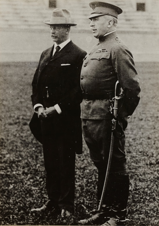A military officer stands with a man in a business suit.