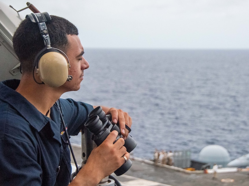 Seaman Carlos Diaz, from Minneapolis, Minnesota stands port watch on the bridge wing of the U.S. Navy's only forward-deployed aircraft carrier USS Ronald Reagan (CVN 76).