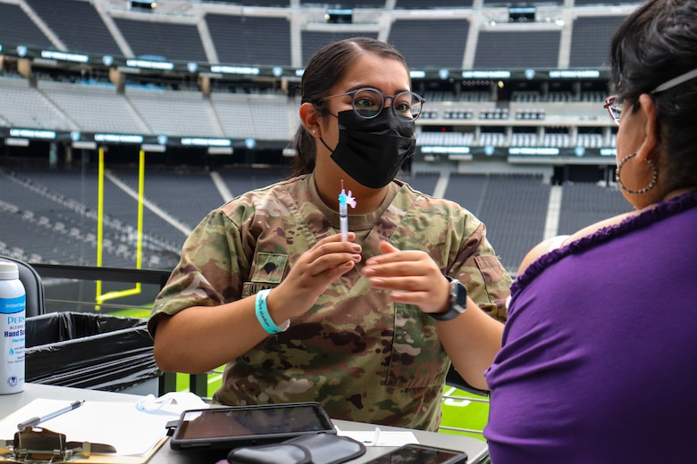 Nevada National Guard Spc. Dulce Alaniz with Joint Task Force 17 prepares to administer the one-shot Janssen vaccine to a citizen at Allegiant Stadium in Las Vegas June 10, 2021. The Nevada Guard is winding down it's 16-month battle against the coronavirus.