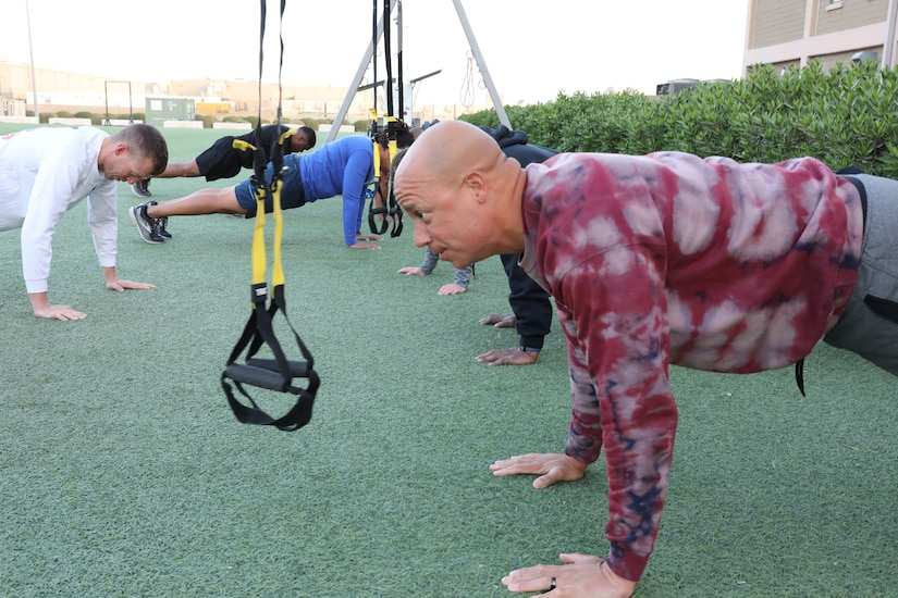 Maj. Anthony Sims-Hall, 1st Theater Sustainment Command, theater mortuary affairs officer, leads a workout for Soldiers at Camp Arifjan, Kuwait.  Sims-Hall prepares functional fitness classes for Soldiers while deployed in order to assist in their preparation for the newly implemented Army Combat Fitness Test (ACFT).