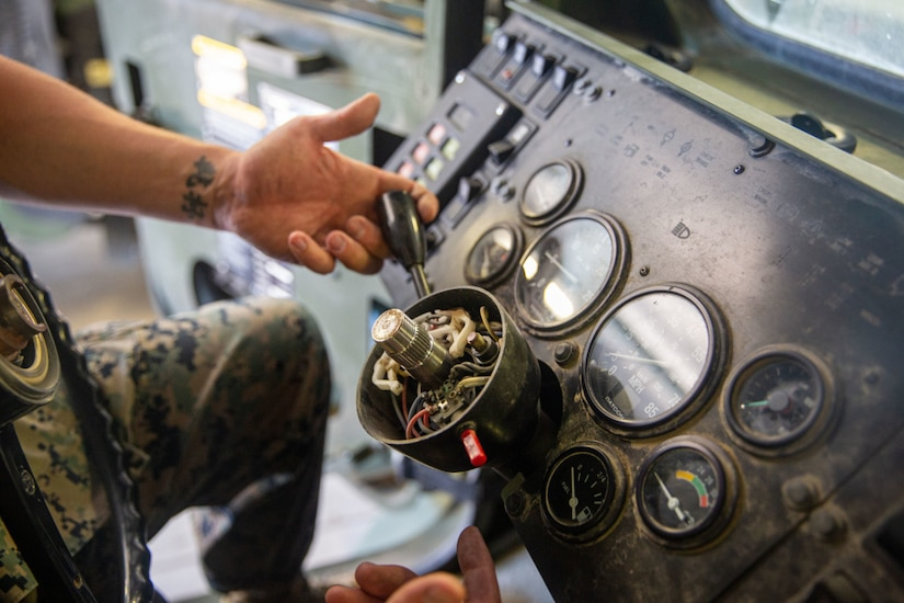 Staff Sgt. Kyle Owens, a motor transportation chief with Combat Logistics Battalion 5, 1st Marine Logistics Group, I Marine Expeditionary Force, shows the wire housing found inside that steering wheel column of the Medium Tactical Vehicle Replacements at Marine Corps Base Camp Pendleton, April 29, 2021. When troubleshooting lighting issues, mechanics are often required to remove the steering wheel to access the wiring. Traditionally, a 10-way slide hammer kit is used to remove the wheel, often cracking the column or warping the wheel in the process. Owens designed a tool that prevents any damage to the truck while removing the steering wheel that won him an Operational Agility Team award for the Innovation Challenge.