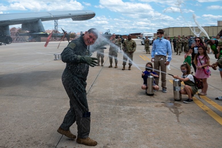 U.S. Air Force Col. John Gonzales, 51st Fighter Wing commander, is sprayed with water by his children after his final A-10 Thunderbolt II flight at Osan Air Base, Republic of Korea, June 16, 2021. Gonzales' family and friends met him on the flightline to celebrate this event. (U.S. Air Force photo by Senior Airman Branden Rae)
