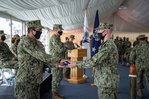 210615-N-KZ419-1229 NAVAL SUPPORT ACTIVITY BAHRAIN (June 15, 2021) Coast Guardsmen present pennants from the USCGC Adak (WPB 1333) and USCGC Aquidneck (WPB 1309) during the decommissioning ceremony for Adak and Aquidneck onboard Naval Support Activity Bahrain, June 15. Adak and Aquidneck operated in the U.S. 5th Fleet area of operations since 2003 in support of Operation Iraqi Freedom, Enduring Freedom, Inherent Resolve and Spartan Shield. (U.S. Navy photo by Mass Communication Specialist 3rd Class Dawson Roth)