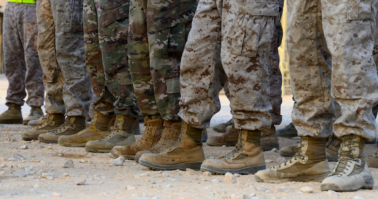 Air Force and Marine Corps personnel stand in formation before morning physical training.
