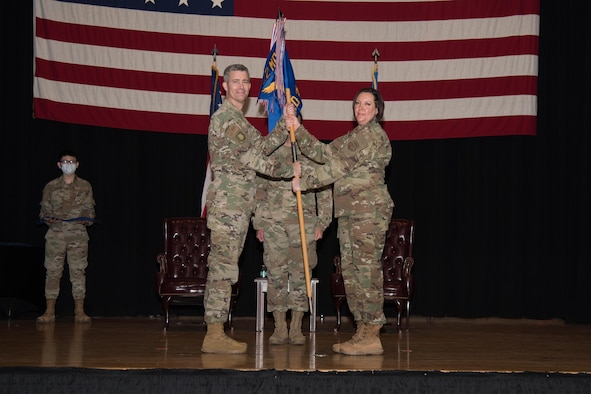 Lt. Col. Angela Yuhas, 22nd Medical Support Squadron outgoing commander, right, relinquishes command during an in-activation ceremony June 16, 2021, at McConnell Air Force Base, Kansas. During Yuhas' command she led 98 Airmen over two years of service in the 22nd Medical Group. The in-activation ceremony was held in order to merge the squadron with the 22nd Healthcare Operations Squadron. (U.S. Air Force photo by Senior Airman Alexi Bosarge)
