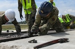 Michigan Air National Guard power production Airmen from the 110th Civil Engineer Squadron and the Alpena Combat Readiness Training Center remove a fairlead beam June 8, 2021. They replaced the aircraft arresting system, which helps stop aircraft with tailhooks in case of emergency.
