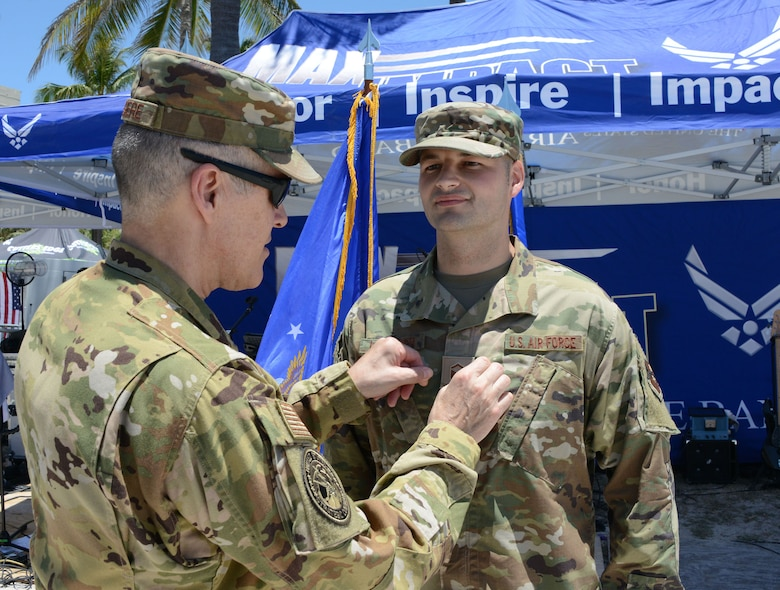Lt. Gen. Thomas Bussiere, U.S. Strategic Command deputy commander, pins master sergeant rank on Doryan Leterrier, 333rd Recruiting Squadron Enlisted Accessions recruiter, during a promotion ceremony on the beach at the Miami Beach Air Show, May 28, 2021.