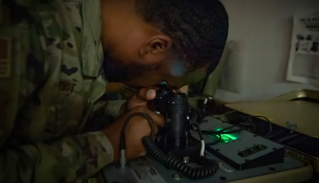 An Airman inspects night vision goggles.
