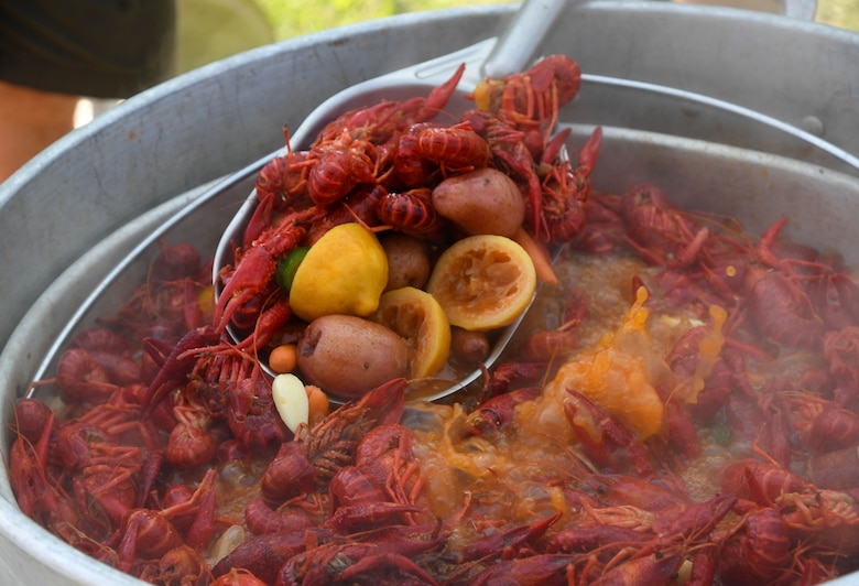 """A pot of boiled crawfish and the """"fixins"""" soak in seasonings during the 9th Annual Crawfish Cook-Off at the Bay Breeze Event Center at Keesler Air Force Base, Mississippi, June 11, 2021. Twelve teams competed in the event and more than 800 pounds of crawfish were distributed. (U.S. Air Force photo by Kemberly Groue)"""