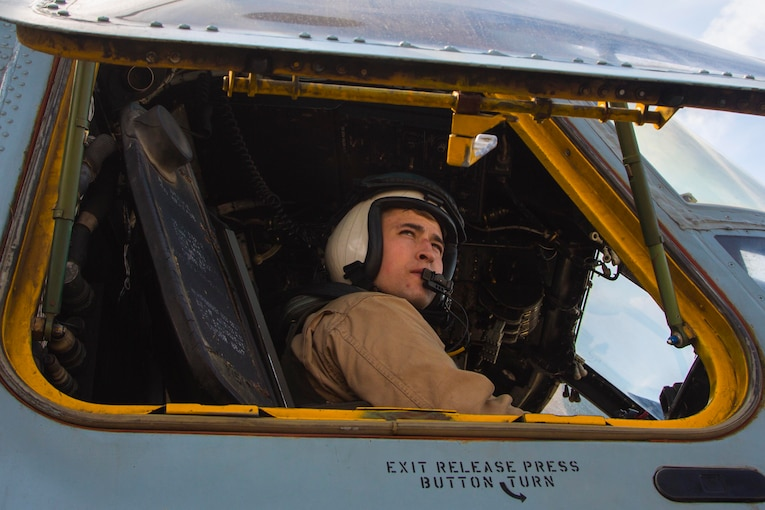 A Marine sits in the cockpit of an aircraft.
