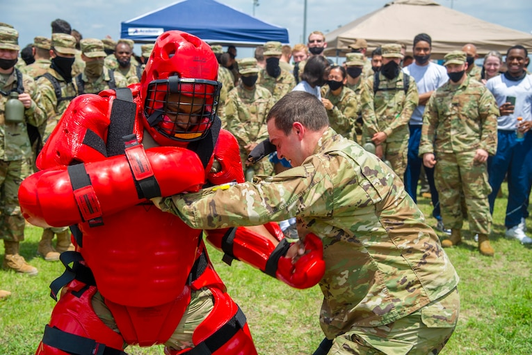 An airman wearing protective gear blocks a punch from another airman.