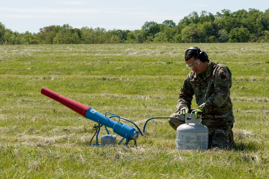 U.S. Air Force Master Sgt. Jose Marrero, noncommissioned officer in charge of airfield management with the 167th Operations Support Group, sets up a pyrotechnic propane canon near the runway, as part of the Bird/wildlife Aircraft Strike Hazards (BASH) program, at the 167th Airlift Wing, Martinsburg, West Virginia, May 12, 2021. The airfield management team uses many different types of noise making devices to encourage animals to move away from the airfield to ensure safe flying operations.