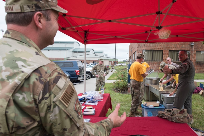 U.S. Air Force Chief Master Sgt. Mark Snyder, right, 167th Airlift Wing loadmaster, tosses a bag of kettle corn to Capt. Clinton Dunham, a 167th personnel officer assigned to the equal opportunity office, who was manning a wellness resources tent as part of the wing's unit training assembly activities at Shepherd Field, Martinsburg, West Virginia, June 12, 2021. The 167th AW Chiefs' Council prepared the kettle corn that was handed out by the Wing Care Team at a tent set up in front of the wing dining facility to help make Airmen aware of the wellness resources available to them.