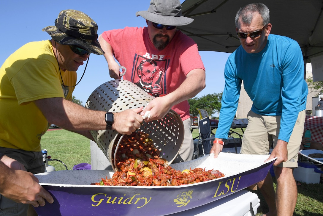 Gary Guidry, Second Air Force curriculum developer, James Reeves, Second AF training requirements action officer, and Joe Taranto, Second AF A3/6 deputy director, pours out a pot of boiled crawfish during the 9th Annual Crawfish Cook-Off at the Bay Breeze Event Center at Keesler Air Force Base, Mississippi, June 11, 2021. Twelve teams competed in the event and more than 800 pounds of crawfish were distributed. (U.S. Air Force photo by Kemberly Groue)
