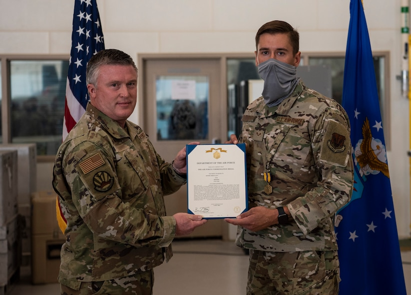 Senior Airman Levi is presented with an Air Force Commendation Medal.