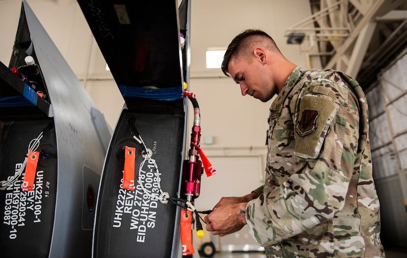 Senior Airman Levi inspects parts of a detached wing from an MQ-9 Reaper.