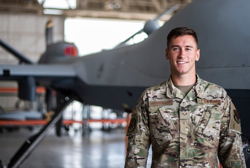 Senior Airman Levi stands to the side of an MQ-9 Reaper and smiles for a photo.