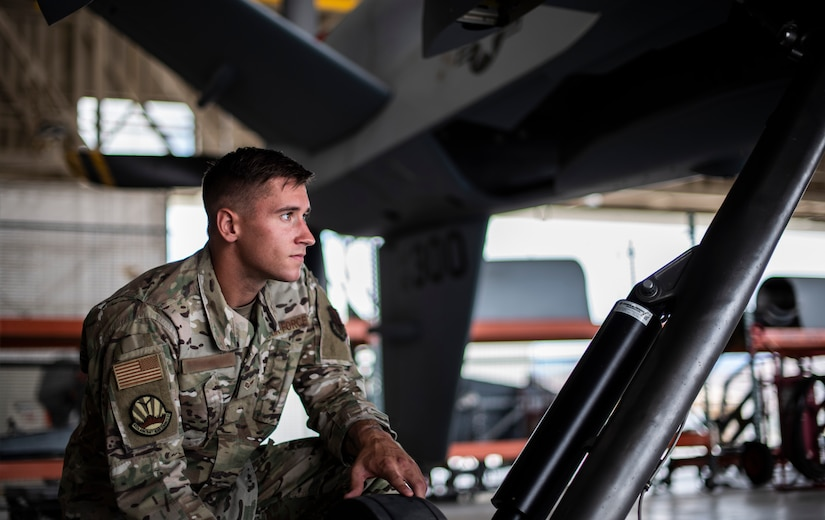 Senior Airman Levi looks up into the distance while under an MQ-9 Reaper.