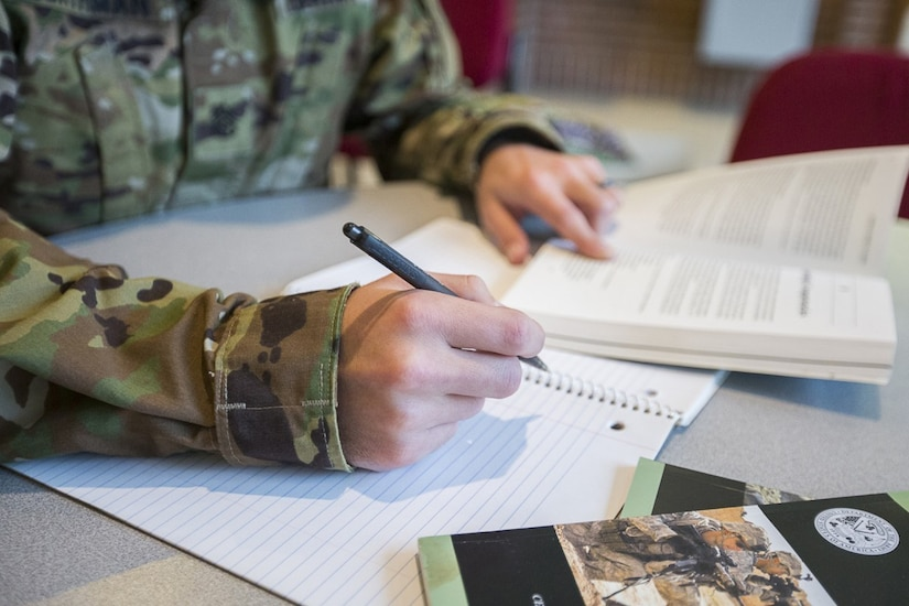 A soldier takes notes during a study session.