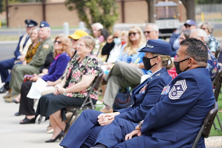 The Commander and command chief of the 146th Airlift Wing watch a speaker speak at a memorial service.