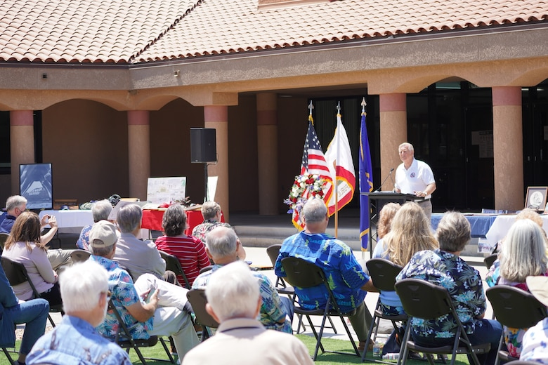 A picture of an alumni guest speaker talking to an audience at a celebration of life inside the heritage square plaza at Channel Islands Air National Guard Station.