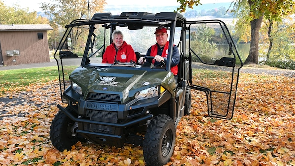 Shirley and John Houser, former camp host volunteers at Swallows Park in Clarkston, sitting in a utility vehicle.