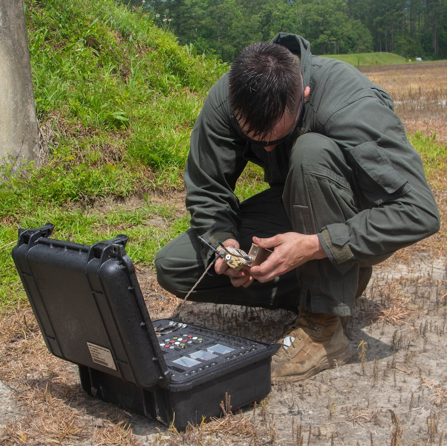 U.S. Marine Corps Sgt. Jonathan Cosgrove, a Marine lateral moving into Explosive Ordnance Disposal (EOD), prepares a remote detonating device at Marine Corps Air Station Cherry Point, North Carolina, June 9, 2021. EOD conducted an ordnance training range with Carteret County Special Forces Teams (SRT) that consisted of classes and demonstrations of the effects of different military ordnance, military explosives and improvised charges in which SRT might encounter. (U.S. Marine Corps photo by Lance Cpl. Symira Bostic)
