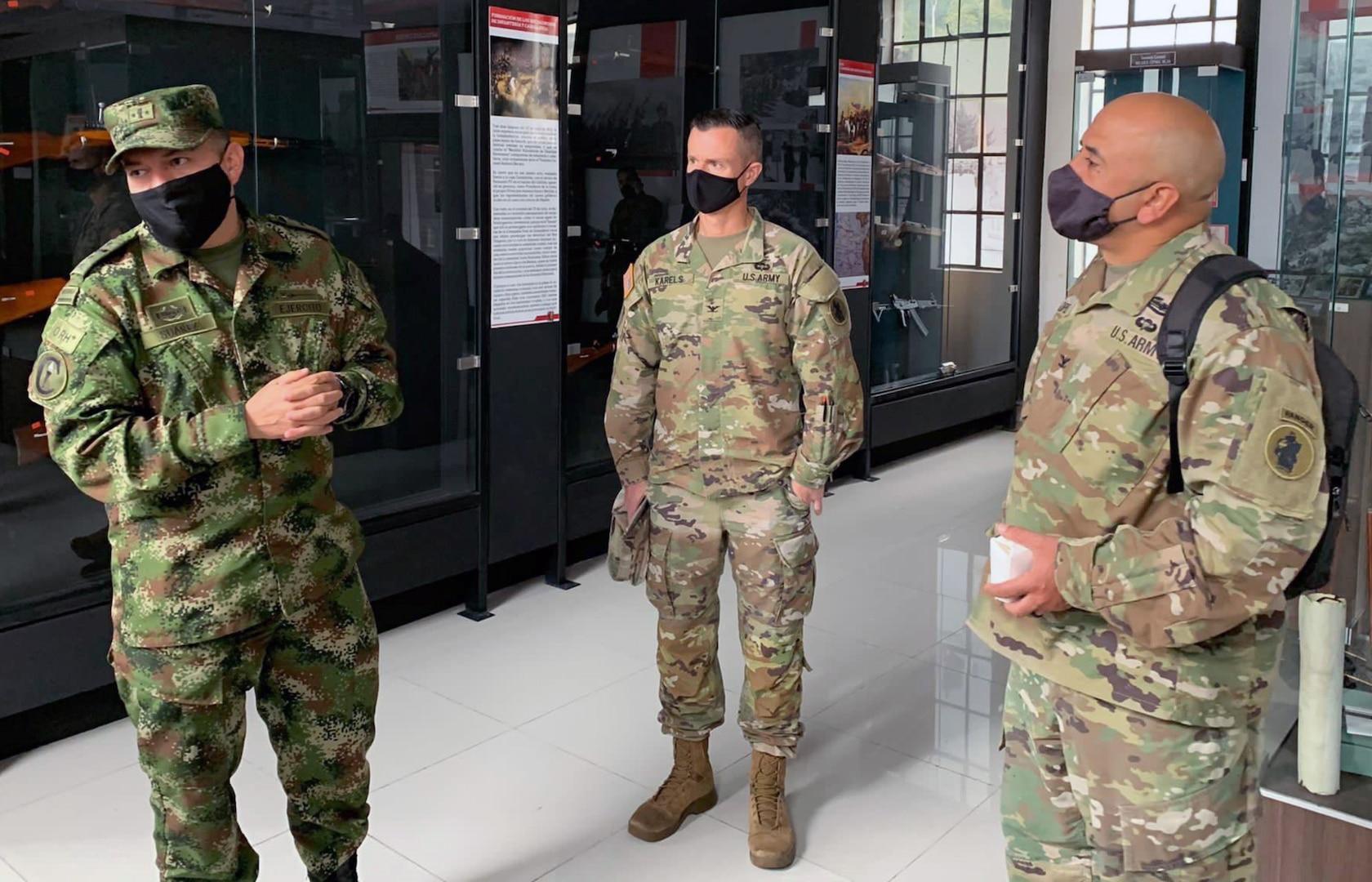 Three men in military uniform stand in hallway