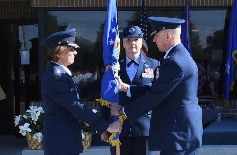 U.S. Air Force Maj. Gen. Andrea Tullos, Second Air Force commander, passes the guidon to Col. William Hunter, 81st Training Wing commander, during a change of command ceremony on the Levitow Training Support Facility drill pad at Keesler Air Force Base, Mississippi, June 17, 2021. The ceremony is a symbol of command being exchanged from one commander to the next. Hunter assumed command of the 81st TRW from Col. Heather Blackwell. (U.S. Air Force photo by Kemberly Groue)