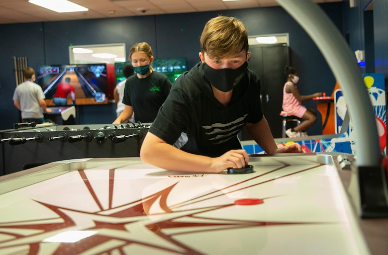 James Smith, 14, plays air hockey as Evelyn Wilbern, 12, checks out the foosball table behind him June 10, 2021, in the Prairies Youth Center's new game room. The venue, which is having its grand opening June 18, features free arcade games. (U.S. Air Force photo by R.J. Oriez)