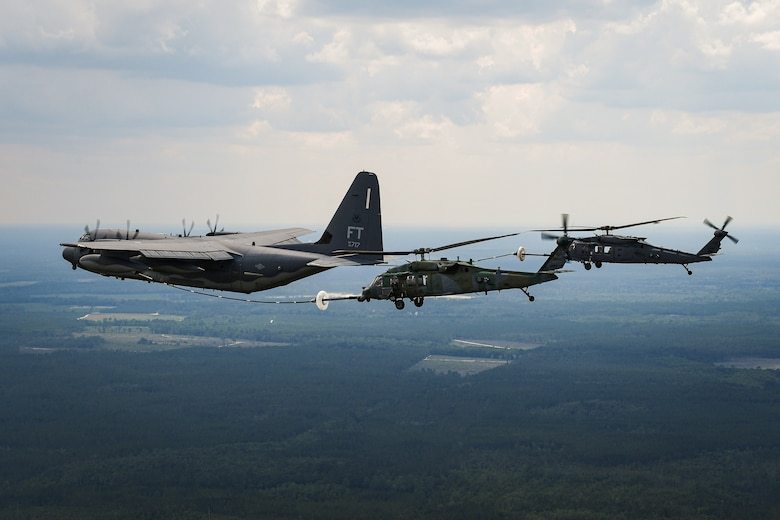 A helicopter receives fuel from a C-130