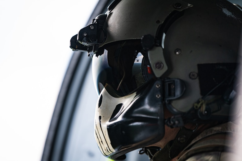 An aviator looks out of a helicopter in flight