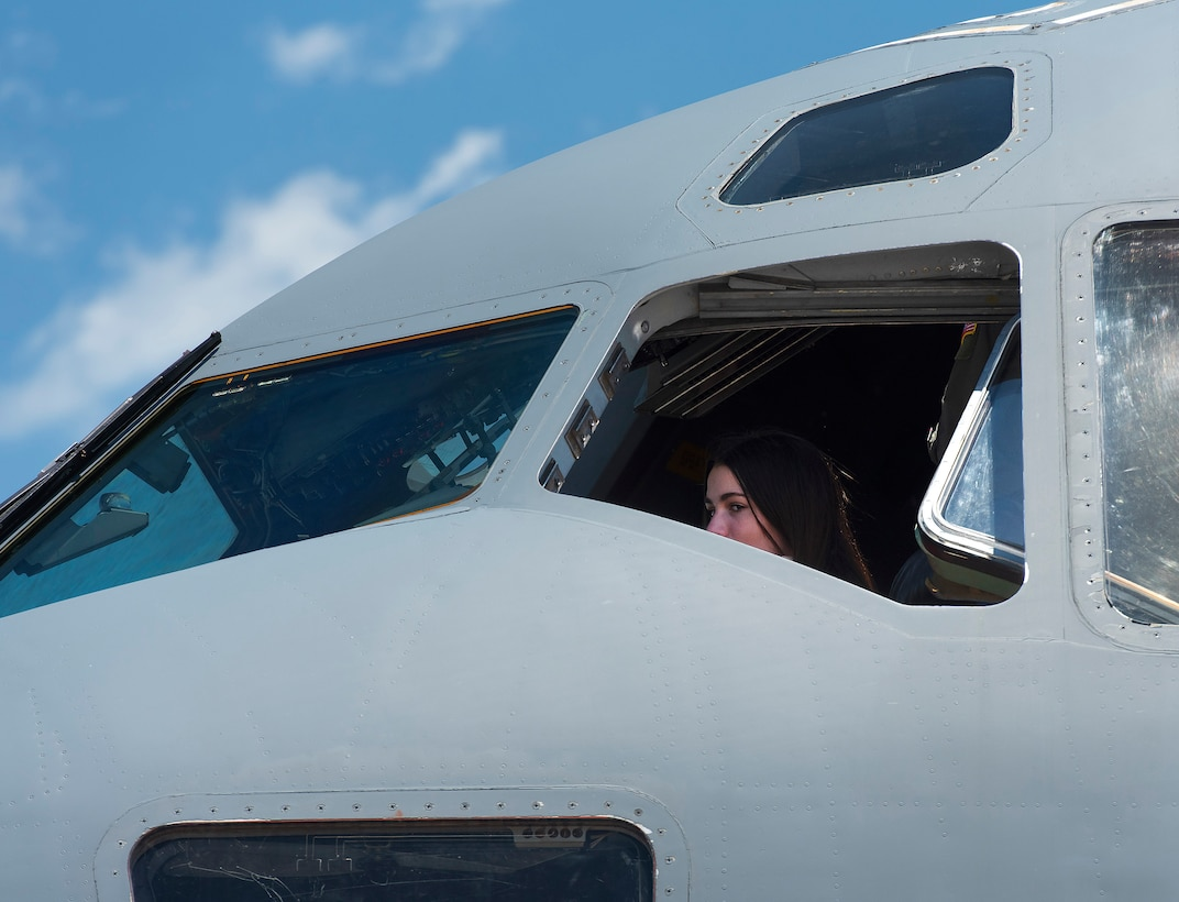 A camper looks out the cockpit window of a C-17 Globemaster III aircraft June 14, 2021, at Wright-Patterson Air Force Base, Ohio. She was taking part in Air Camp, a STEM program set up to raise interest in aviation among middle  school students. (U.S. Air Force photo by R.J. Oriez)