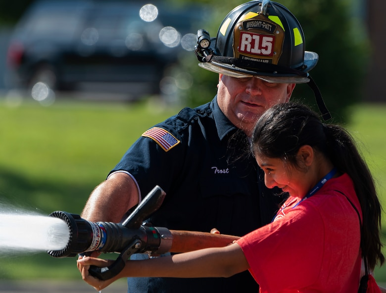 A camper handles a fire hose with the help of firefighter Thomas Trost, 788th Civil Engineer Squadron, at the main fire station on Wright-Patterson Air Force Base, Ohio, June 15, 2021. Air Camp participants came to Wright-Patt to tour aircraft, learn about firefighting and visit the U.S. Air Force School of Aerospace Medicine. (U.S. Air Force photo by R.J. Oriez)
