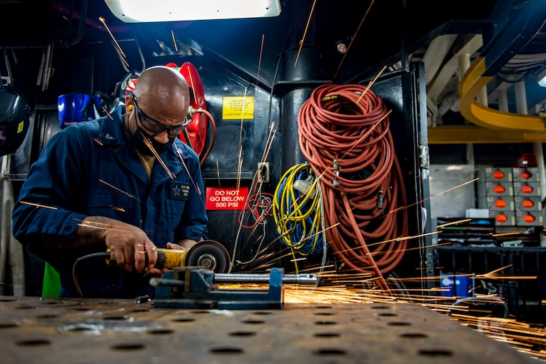 A sailor works with a tool in a shop, creating sparks.