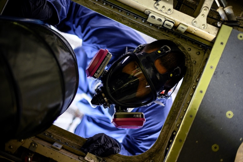 An Airman in a respirator looks up into a compartment of an aircraft.