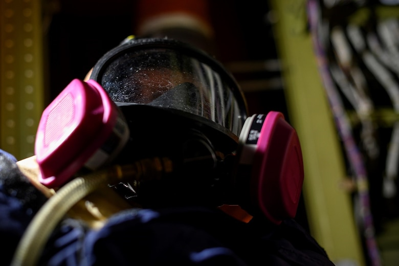 A training dummy in a respirator sits in a compartment of an aircraft