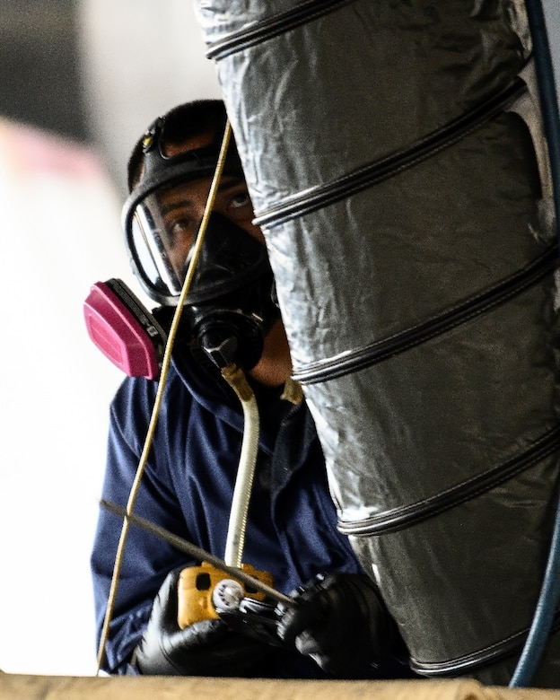 An Airman in a respirator looks up at a long tube that's feeding into the compartment of an aircraft.